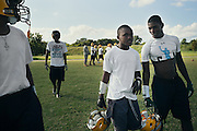 "BIRMINGHAM, AL – SEPTEMBER 10, 2015: Quintarius Monroe (center) speaks with Cornelius Mosley (right) as they break from football practice at Woodlawn High School. A type 1 diabetic, Monroe requires frequent blood sugar testing and supervision when self-administering insulin. When care from qualified personnel at his school in Center Point became unavailable, Monroe was forced to transfer several miles away from his locally zoned school to attend Woodlawn High School. The Americans with Disabilities Act requires schools to provide ""reasonable accommodation"" for students with medical conditions, but given that most failing public schools no longer retain school nurses, many schools cannot provide adequate care for their students.<br />