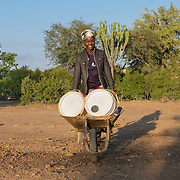CAPTION: Rutendo uses buckets and a wheelbarrow to transport water. More borehole pumps mean more people here will have easier access to water for household use, as well as for agriculture. LOCATION: Mawoneke Village, Chivi District, Masvingo Province, Zimbabwe. INDIVIDUAL(S) PHOTOGRAPHED: Rutendo Gozo.
