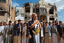 Wearing his ceremonial dagger, Yemen's top tribal leader, Sheikh Sadiq al Ahmar, and his tribesmen stand by his residence, with its portrait of al Ahmar's politician father in Sana, Yemen, April 6, 2012. The sheikh's followers fired on government troops in May 2011; they retaliated, attacking his home.