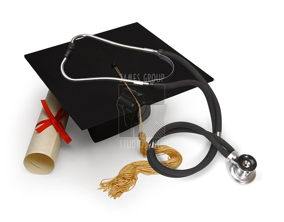 mortar board, diploma and stethoscope on white