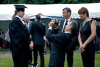 Graduating Student being photographed by his father  at Cambridge University Graduation Day 2007.
