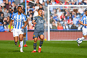 Youri Tielemans of Leicester City (21) and Steve Mounie of Huddersfield Town (24) in action during the Premier League match between Huddersfield Town and Leicester City at the John Smiths Stadium, Huddersfield, England on 6 April 2019.