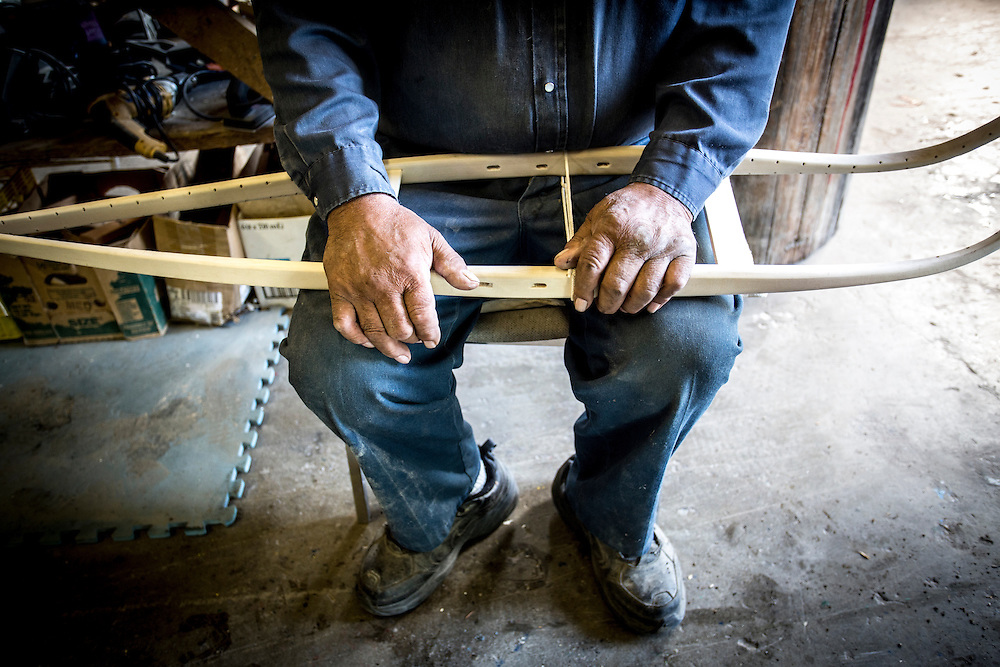 Doug Smarch holds an incomplete snowshoe as he explains the building process at his workshop in Teslin, Yukon.