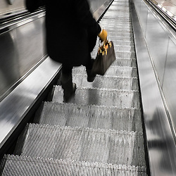 A commuter walking down an escalator.