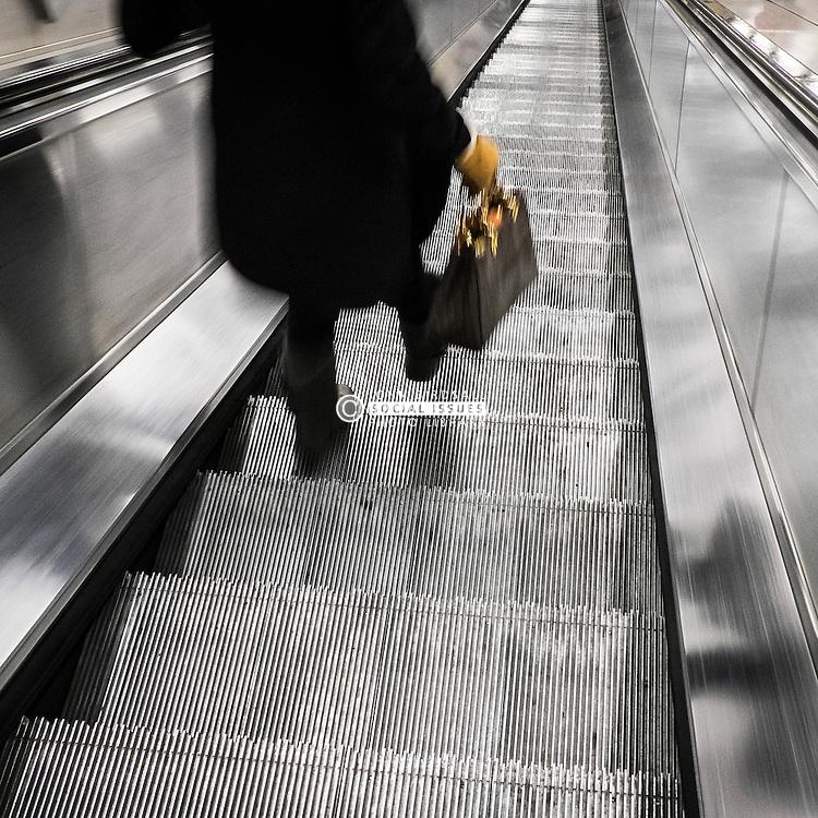 A commuter walking down an escalator.