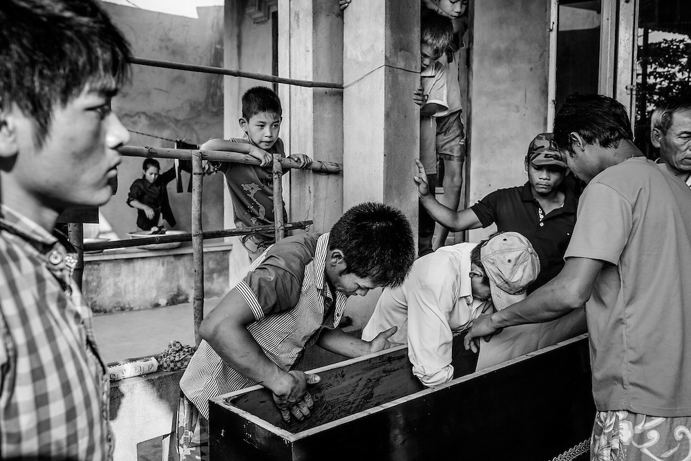 Men prepare the coffin for Ngo Chan Khang, 5, who lost his life in an accidental drowning just hours prior. In following Buddhist Vietnamese tradition, the body is displayed and mourned in the home in the hours directly following the death, then put into the casket on the evening of the first day. It it then kept in the home and morned for two more days before being buried or cremated, following the third day of lamentations.Phu Mau Village, Hue, Vietnam. March 3, 2015