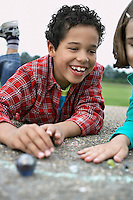 Boy and girl (7-9) playing marbles in playground