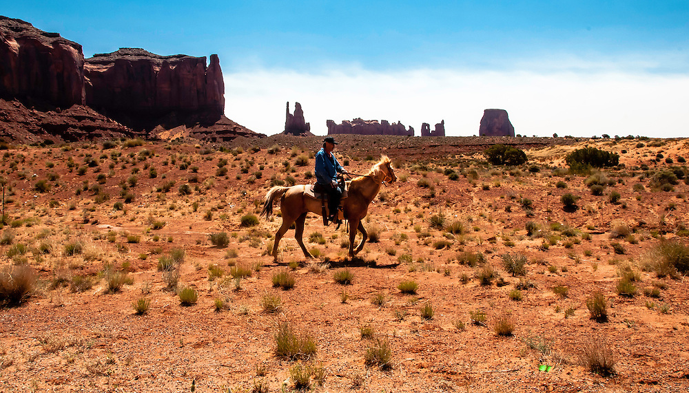 Horseman riding in the vast landscape of Monument Valley, Arizona.