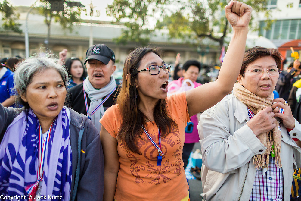 """01 JANUARY 2014 - BANGKOK, THAILAND:  Anti-government protestors sing the Thai national anthem and chant """"Long Live the King!"""" during a special merit making ceremony in the protest camp. Thousands of anti-government protestors are camped out at Democracy Monument in central Bangkok protesting against the government of Yingluck Shinawatra. The protest leader, Suthep Thaugsuban, has called for residents of the Thai capital to rise up against Yingluck. He has promised to shut the city of 12 million down in his final push to overthrow the government. About 100 members of the Thailand's Buddhist clergy visited the protest site Wednesday morning for a special New Year's day merit making ceremony for the protestors.    PHOTO BY JACK KURTZ"""