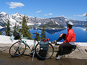 Bicycle in view of Wizard Island, which rises in the deep blue lake at Crater Lake National Park, in Oregon, USA. To allow snow plowing in early June, Rim Drive is closed to cars but open to bicycles, making an excellent time for a bike ride free of automobiles. Published in August 2015 issues of Alaska Airlines & Horizon Edition inflight magazines.