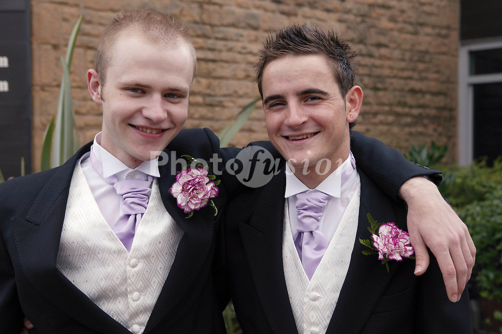 Groom and best man standing outside church smiling,