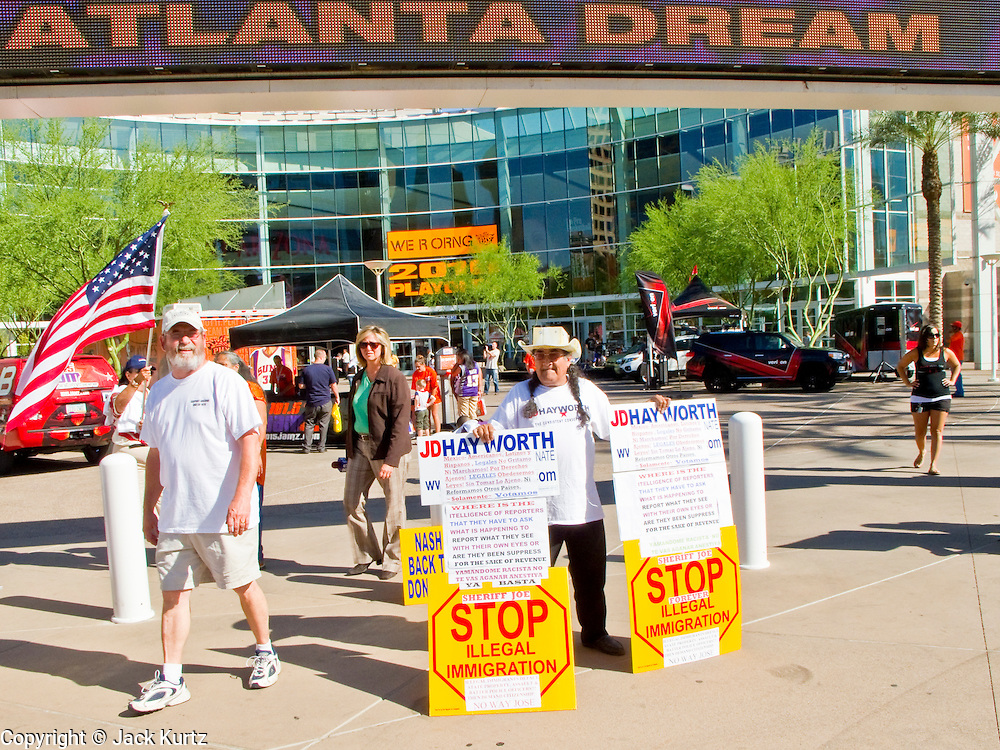 """25 MAY 2010 - PHOENIX, AZ: Picketers in front of US Airways Arena in Phoenix, Tuesday, May 25. People opposed to illegal immigration and in favor of Arizona SB1070 picket the Phoenix Suns playoff game against the Los Angeles Lakers Tuesday. About 10 people attended the protest. One person opposed to SB1070 held a counter demonstration. SB1070 makes it an Arizona state crime to be in the US illegally and requires that immigrants carry papers with them at all times and present to law enforcement when asked to. People are picketing the Suns games because Suns owner Robert Sarver has expressed opposition to the law and has had the Suns wearing jerseys that say """"Los Suns.""""  PHOTO BY JACK KURTZ"""