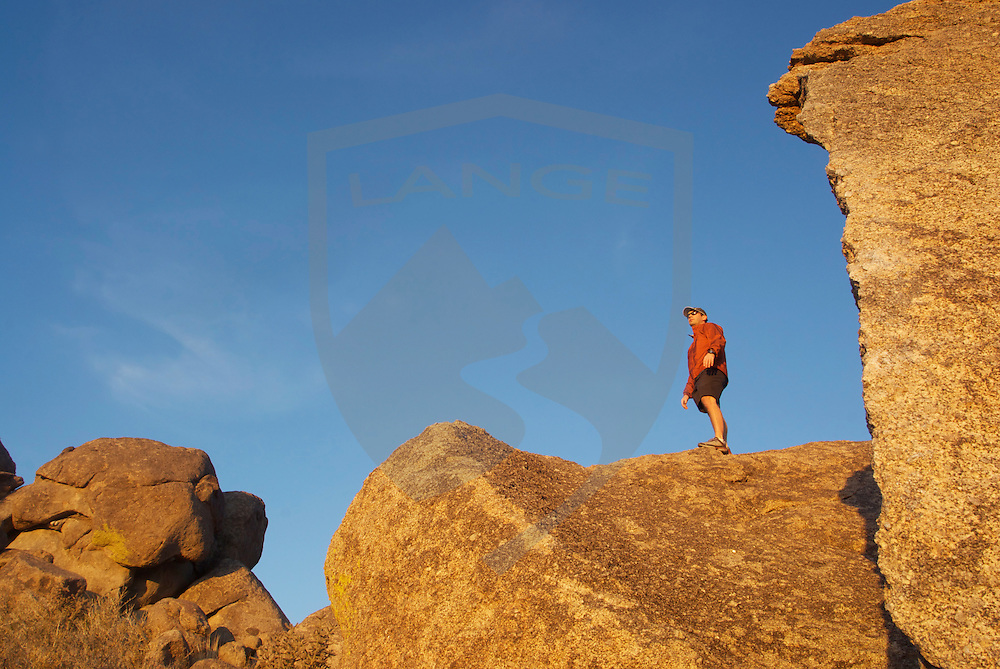 man standing atop limestone boulders and watching the sunset, sandia mountains, albuquerque, new mexico, usa