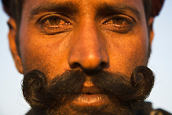 "Close-up portrait of a man with  a ""handlebar"" moustache staring into the camera, sunrise,  Pushkar camel fair, Rajasthan, India"