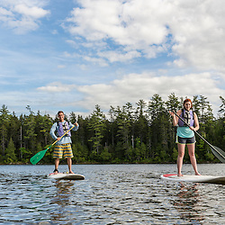 A couple paddleboarding on Long Pond near the Appalachian Mountain Club's Gorman Chairback Lodge. Near Greenville, Maine.