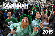 Chris Mitchum, left, and Joe Padgett, right, of Charleston, S.C. battle over beads tossed from a balcony during St. Patrick's Day celebration Saturday, March 14, 2015, on River Street in Savannah, Ga. Thousands of gaudy green visitors are in Savannah this weekend for to kick off a four-day celebration that peaks Tuesday with the St. Patrick's Day parade. (AP Photo/Stephen B. Morton)