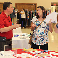 Madison Caver, a case manager at SAFE, talks with Brad Gates, WIOA Career Services Director at ICC, as she walks the different vendor booths to gather information that will help her clients during a homeless job fair at All Saints Episcopal Church in Tupelo Thursday morning.