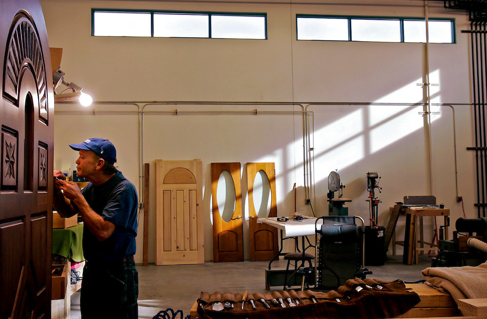 "Xavier Mascareñas/The Daily Time; Jay Fann, small business owner of Mancos Doors LLC, works on a wall hanging he called ""Madonna and Child"" in his discounted commercial space offered by the business incubator at San Juan College's Quality Center for Business on Friday."
