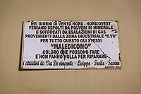 """TARANTO, ITALY - 22 FEBRUARY 2018: A plaque saying """"During the days North-North-West wind, we are buried by mineral dust and suffocated by gas emissions coming from the ILVA industrial plant. For this reason we damn those who could and won't do anything to fix this"""", in Tamburi, the working-class district adjacent the ILVA steel mill in Taranto, Italy, on February 22nd 2018.<br /> <br /> Taranto, a  formerly lovely town on the Ionian Sea has for the last several decades been dominated by the ILVA steel mill, the largest steel plant in Europe. It was built by the government in the 1960s as a means of delivering jobs to the economically depressed south, but has been implicated for a cancer as dioxin and mercury have seeped into local groundwater, tainting the food supply, while poisoning the bay and its once-lucrative mussels."""