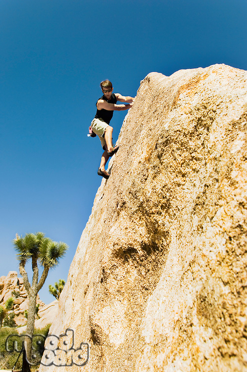 Woman Free Climbing on Cliff side view