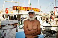 Lampedusa, Italia 2 luglio 2011. Il comandante Giacomo Brignone ritratto davanti al suo battello per gite in barca intorno all'isola di Lampedusa. A causa del calo del turismo il comandante Brignone è costretto molto spesso a rimanere ormeggiato in porto..Ph. Roberto Salomone Ag. Controluce