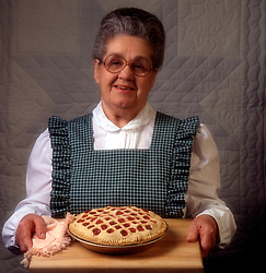 Frilly apron smiling woman female quilt background  Woman serving lattice crust cherry pie