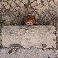 Random doll on a sidewalk.