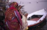 Woman praying facing the Ganga in Benares, India // FEMME PRIANT FACE AU GANGE, SUR LES GHATS DE BENARES, INDE. Bénarès, ou Varanasi, située sur les bords du Gange en Inde du Nord, est la ville sacrée la plus importante de toute l'Inde. C'est là que tous les fidèles hindouistes rêvent d'aller mourir.