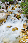 The clear stream from Pericnik Waterfall flows over rocks colored yellow from algae in Vrata Valley, near Mojstrana, Slovenia, Europe. A fun trail passes behind the falls through a cave. The scenic Vrata valley extends from Mojstrana village to the north face of Triglav, in Triglavski narodni park, Slovenia's only national park. In 1991, Slovenia declared full sovereignty from Yugoslavia. 80% of its 2 million people speak Slovene. In 2004, Slovenia joined NATO and the EU (European Union), and later adopted the Euro € currency. Slovenia is the richest Slavic nation per capita.