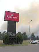 Heavy smoke from an approaching forest fire drifts toward the parking lot of the Ramada Inn on the south end of Business-75 in Grayling.