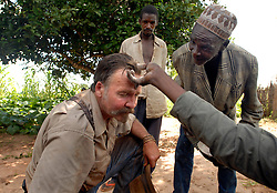 Dairen Simpson is blessed by a local bush doctor as villagers look on in Simana, Tanzania. Ami Vitale