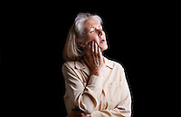 Senior woman suffering with toothache against black background