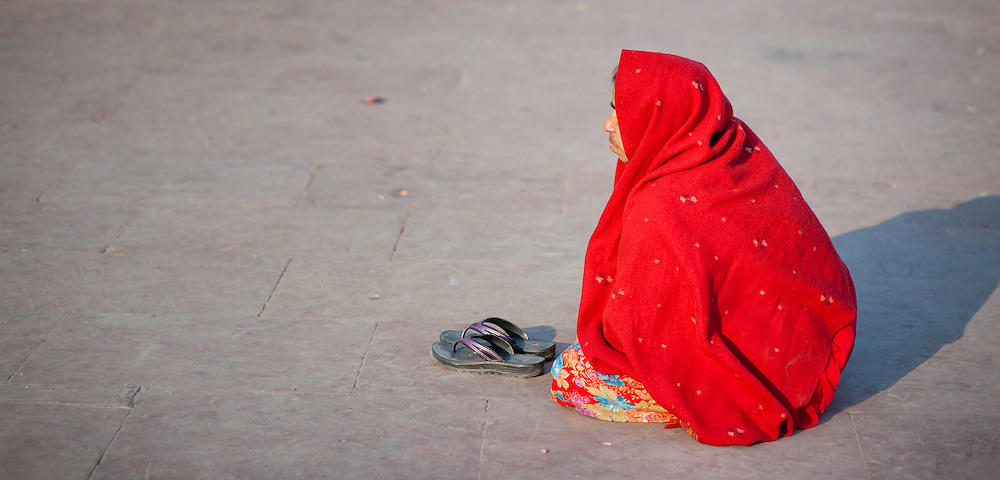 Woman wrapped in red sari squatting (India)