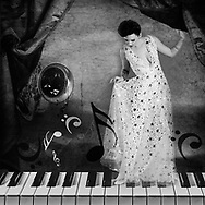 Black and white photo collage of a woman with star covered dress standing on a piano keyboard pushing away a curtain with a saxophone and musical notes in the background