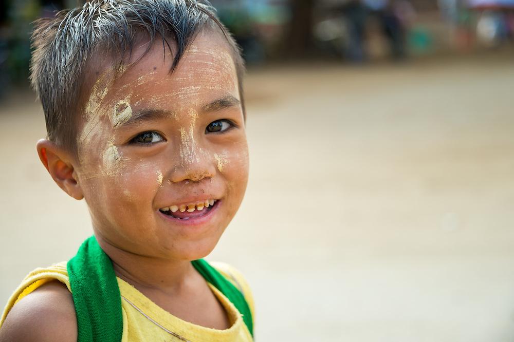 MANDALAY, MYANMAR - CIRCA DECEMBER 2013: Happy Burmese kid smiling and looking at camera playing in the streets of Min Kun in Myanmar
