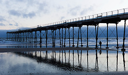 © Licensed to London News Pictures. 10/03/2014<br /> <br /> Saltburn, Cleveland, United Kingdom<br /> <br /> A photographer takes pictures of the pier at first light in Saltburn by the Sea in Cleveland.<br /> <br /> Photo credit : Ian Forsyth/LNP