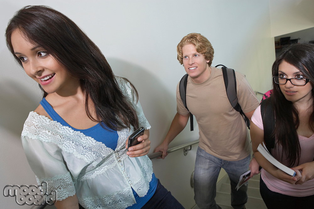 Three students on stairs at school, smiling