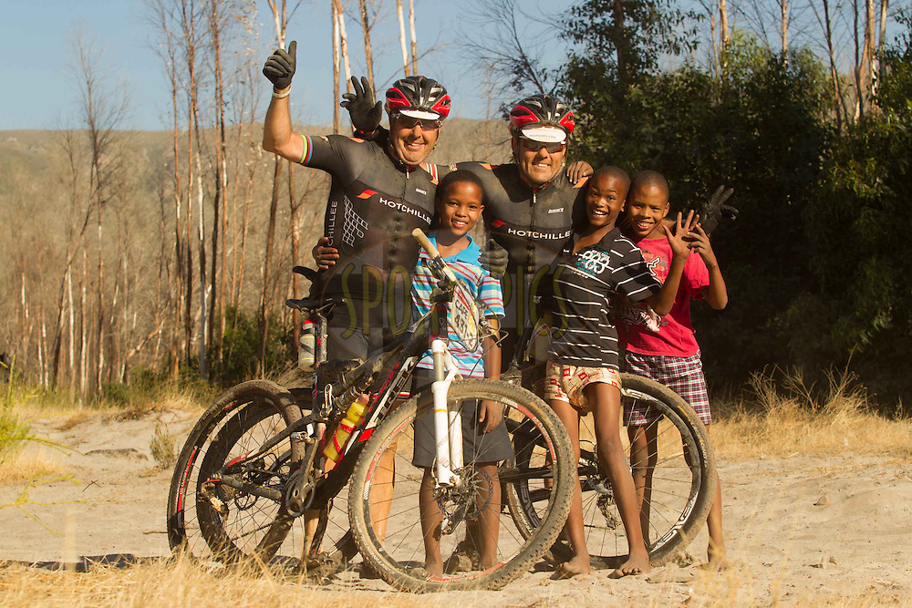 Stephen Roche (left) and Sven Thiele take tie out to pose with local kids for a photo during stage 4 of the 2013 Absa Cape Epic Mountain Bike stage race from Saronsberg Wine Estate in Tulbagh to Wellington, South Africa on the 21 March 2013..Photo by Greg Beadle/Cape Epic/SPORTZPICS