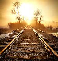 Railroad tracks into the sunrise near the Provo River on a foggy late winter morning.