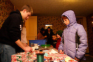 Ben Hansen, 16 of Centerville (left) helps out in the historic Smith home in Bill Yeck Park, part of the Centerville-Washington Township Park District, Friday, December 17, 2010.  The Smith house had hot chocolate and music for those on the Holiday Stroll and luminaria walk.