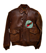 "This type A-2 flight jacket belonged to William E. Hofer, a radio operator attached to the 568th squadron of the 390th Bomb Group. The 568th squadron insignia patch, a panther riding a bomb, is attached to the front left of the jacket. The 8th Air Force insignia patch is attached to the left sleeve of the jacket. The name of Hofer's aircraft, ""Ole Smoke"", is painted in yellow on the back of the jacket. Hofer flew 23 missions over Europe as a member of the 568th squadron. On his 23rd mission, a raid to Augsburg, Germany on March 16, 1944, Hofer and his crew were shot down over Germany and taken as prisoners of war by the Germans."