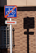 A no-bicycle parking sign in a small laneway in the late afternoon in winter.