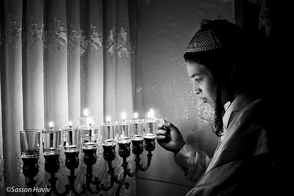 An Orthodox boy lights Hanukkah candles.
