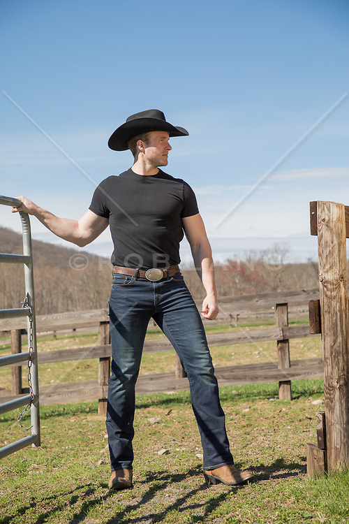 hot cowboy on a ranch opening a gate