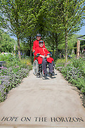 Chelsea Pensioners Jim Lycett and Frank Mouque (wheelchair) and Tom Stimpson   MBE. RAF Veteran on the Hope on the Horizon garden.  The<br /> 'Hope on the Horizon' garden in aid of Help for Heroes: produced by building and landscaping firm Farr and Roberts', making their debut; designed by Matthew Keightley (29), as a result of his brother Michael's involvement with the armed forces, having served on four tours to Afghanistan and due for his fifth this year; and sponsored by the David Brownlow charitable foundation. The garden layout is based on the shape of the Military Cross, the medal awarded for extreme bravery. Granite blocks will represent the soldiers' physical wellbeing and the planting represents their psychological wellbeing at various stages of their rehabilitation. Both evolve through the garden from a rough, unfinished, over-grown beginning through to a perfectly sawn, structured end. An avenue of hornbeams draws the attention through the entire garden to a sculpture resembling a hopeful horizon; a reminder to the soldiers that they all have a bright future ahead. As well as areas to recline and reflect, the garden offers focal points all the way through. Cool, calming colours are used throughout, helping to emphasise the fact that it will be a serene, contemplative space. After the Show, the garden will be moved and set within the grounds at Help for Heroes Recovery Centre at Chavasse VC House in Colchester, Essex. The garden will offer a serene, peaceful haven to contemplate and inspire a bright future and to support the challenging journey to recovery. The Chelsea Flower Show 2014. The Royal Hospital, Chelsea, London, UK