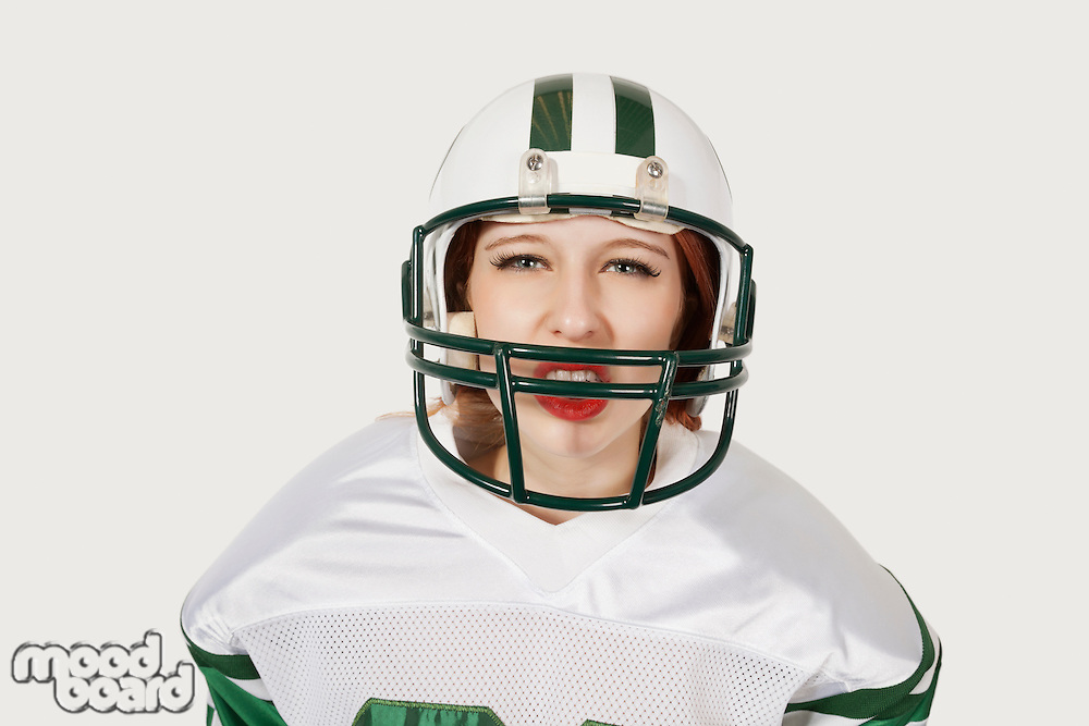 Portrait of woman in football uniform against gray background