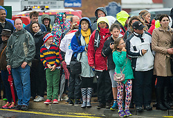 © London News Pictures. 26/07/2015. Members of the public queue in wet weather to see Catherine, Duchess of Cambridge at Land Rover BAR (Ben Ainslie Racing) in Portsmouth, South Hampshire, as part of a visit to the America's Cup World Series with Prince William. Photo credit: Ben Cawthra/LNP