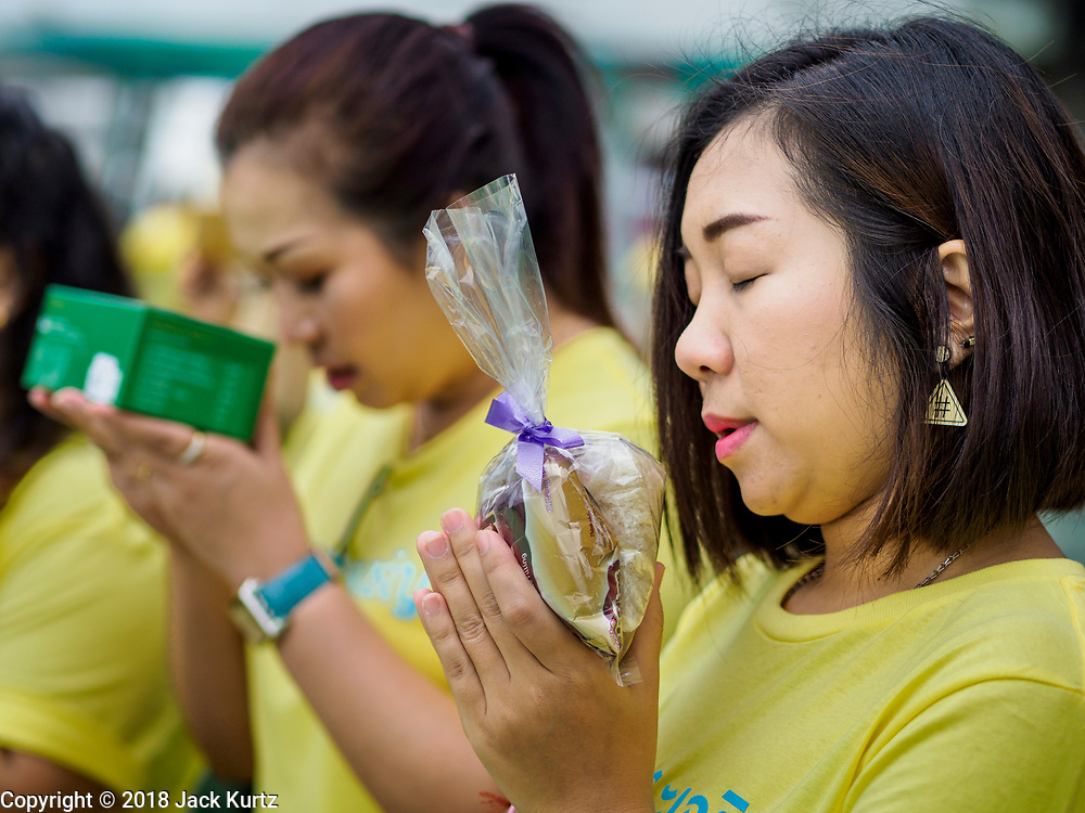 26 JULY 2018 - BANGKOK, THAILAND:  Women pray with the items they are donating to monks during a merit making ceremony in the Pathumwan area of Bangkok to honor Thai King His Majesty King Maha Vajiralongkorn Bodindradebayavarangkun, also known as Rama X, for his 66th birthday. The King's birthday is 28 July, and events are scheduled throughout Thailand to honor His Majesty. The Pathumwan merit making was organized by businesses in the area.      PHOTO BY JACK KURTZ