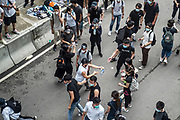 Protesters pass construction gloves to each other to tear down barricades in front of the Central Government Offices, during a protest against a proposed extradition law in Hong Kong, SAR China, on Wednesday, June 12, 2019. Hong Kong's legislative chief postponed the debate on legislation that would allow extraditions to China after thousands of protesters converged outside the chamber demanding the government to withdraw the bill. Photo by Suzanne Lee/PANOS