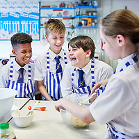 A photograph of school children as they cook in a food technology class in school.